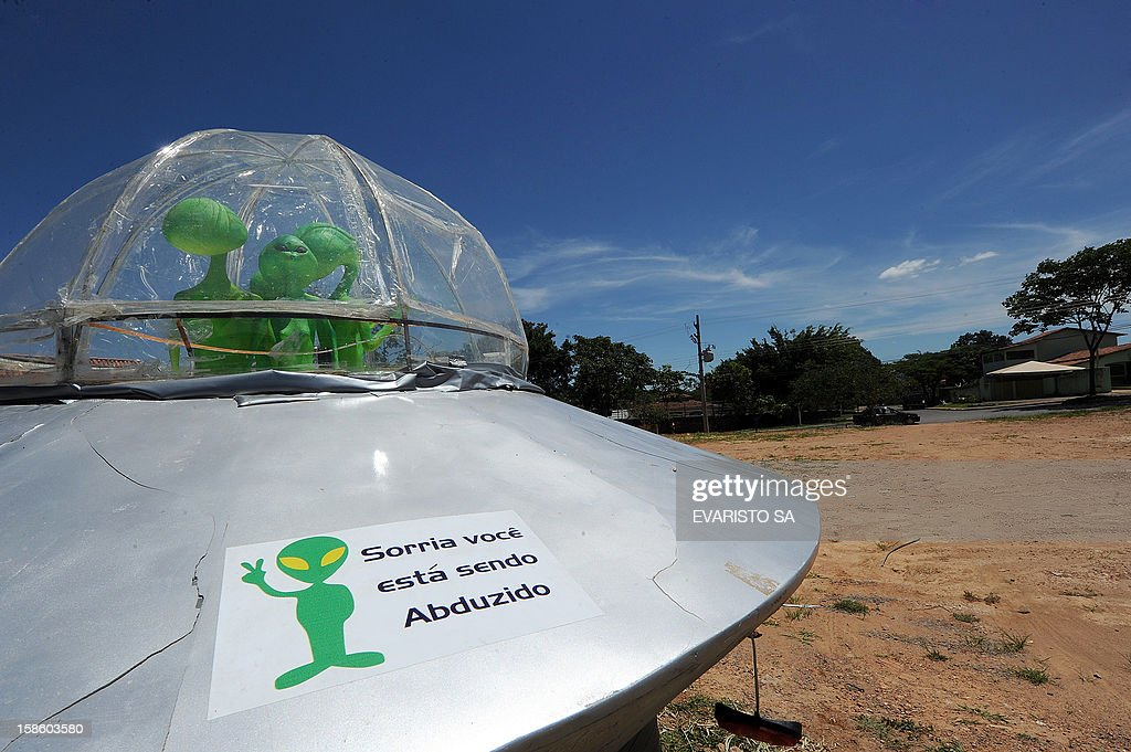 A mock UFO with alien dolls and reading 'Smile, you are being abducted' is seen in Alto Paraiso town, Goias State, 230 kms north of Brasilia, on December 20, 2012. Situated over a huge quartz crystal plate, Alto Paraiso attracted many Brazilians and foreigners seeking refuge from the events expected by the Mayan prophecy that predicts the end of the world or the beginning of a new era. AFP PHOTO / Evaristo SA