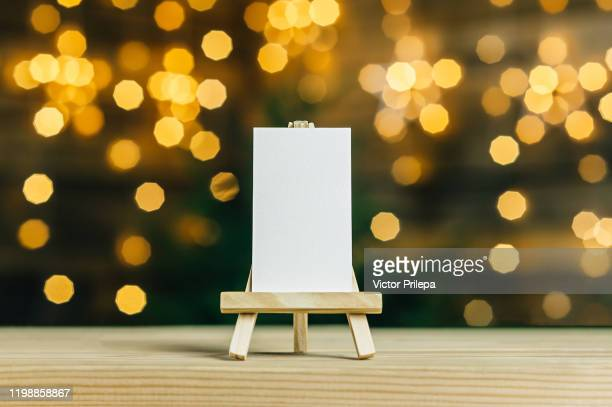 mock up mini easel with a white business card. against the backdrop of a bokeh of stars garland. - focus on background stock pictures, royalty-free photos & images