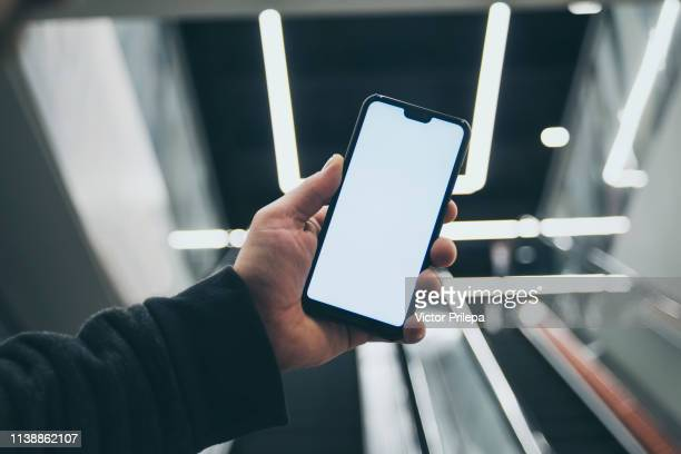 mock up of a smartphone in hand, on the background of an escalator in a shopping center and luminous lamps. - template stock pictures, royalty-free photos & images