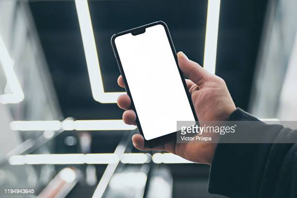 mock up of a smartphone in hand, on the background of an escalator in a shopping center and luminous lamps. - smartphone stock-fotos und bilder