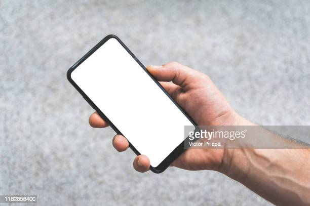 mock up of a smartphone in hand, on the background of concrete tiles. - tenere foto e immagini stock