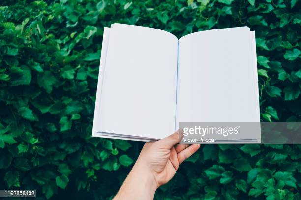 mock up of the book in hand man, against the background of green leaves. concept on the topic of education - back to school. - blank magazine ad stock pictures, royalty-free photos & images