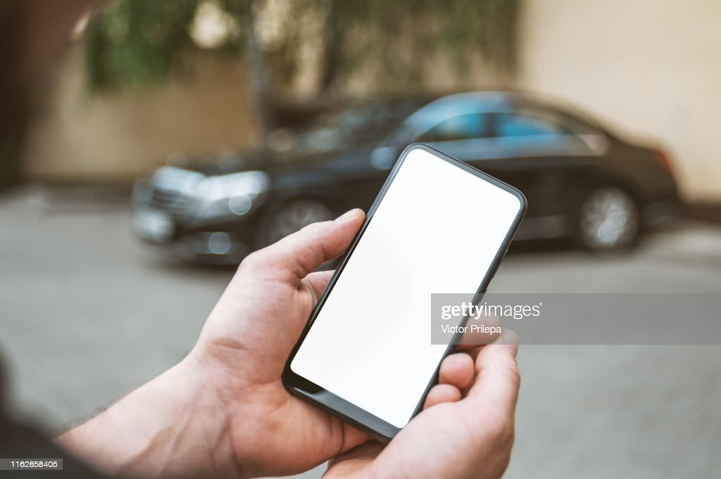 Mock Up Smartphone in man's hand, in the background a black car. : Stock Photo