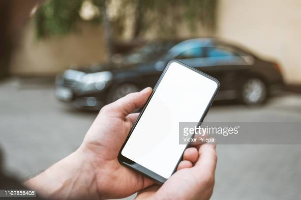 mock up smartphone in man's hand, in the background a black car. - iphone mockup stock pictures, royalty-free photos & images