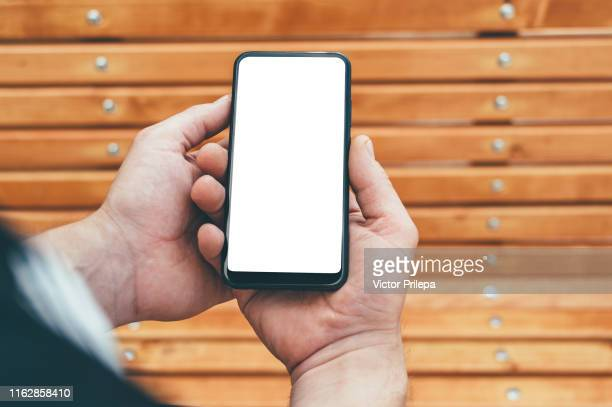 mock up smartphone in the hands of a man, against the background of a wooden bench. - 人工的 ストックフォトと画像