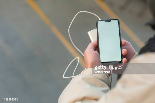 mock up smartphone with portable charging in the hands of a man. - iphone mockup stock pictures, royalty-free photos & images