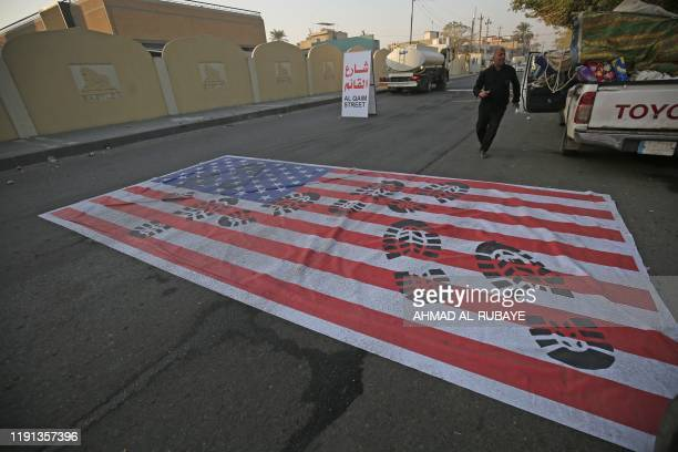 TOPSHOT A mock US flag is laid on the ground for cars to drive on in the Iraqi capital Baghdad on January 3 following news of the killing of Iranian...