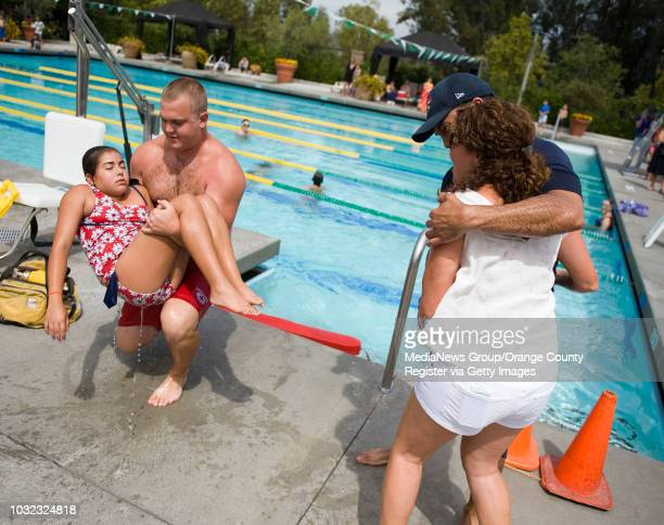 Mockdrowning victim Katrina Silva is carried out of the water by lifeguard Andrew Maass of Mission Viejo as parents Dan and Teri Silva react at right...