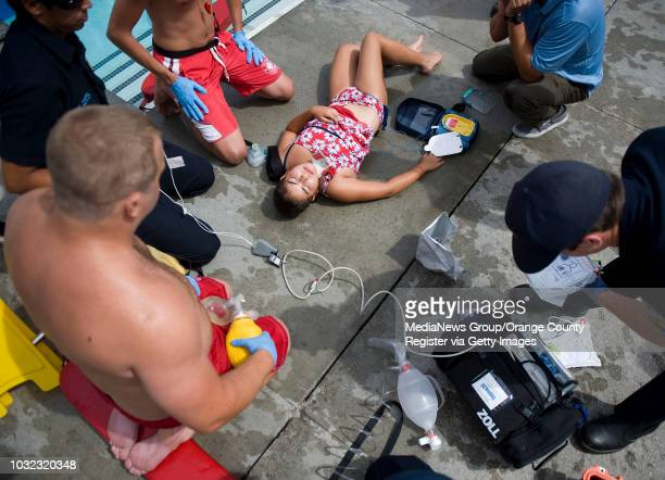 Mockdrowning victim Katrina Silva is tended to by lifeguards and Orange County Fire Authority personnel during Water Safety Day at the Sierra...