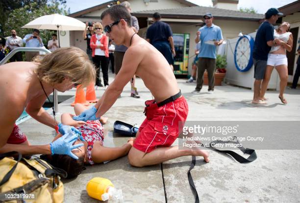 Mockdrowning victim Katrina Silva is tended to by lifeguards Zachary Guns of Mission Viejo left and Nate Hunnicutt of Boise Idaho during Water Safety...