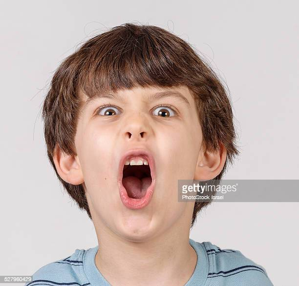 mocking boy pulls face - ugly kids stock photos and pictures