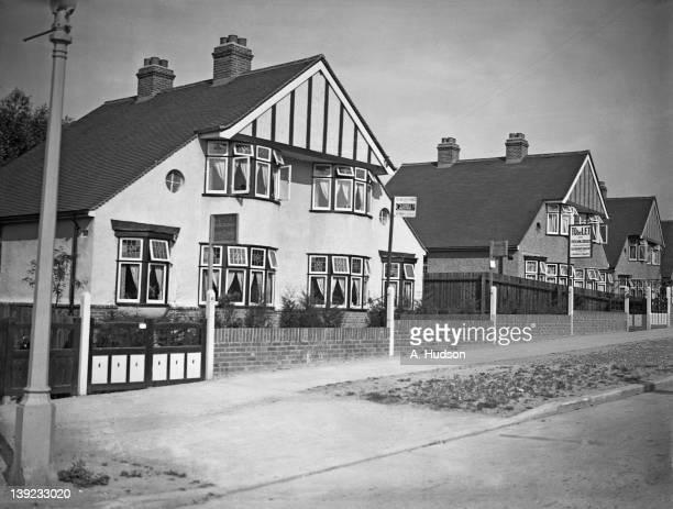 Mocktudor semidetached houses on a suburban street UK July 1933