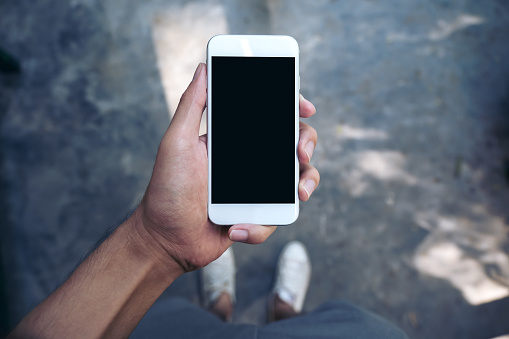 Mockup image of a man's hand holding white mobile phone with blank black screen while standing on concrete polishing floor 895945138