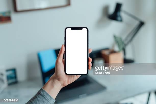 mockup image of woman holding smartphone with blank white screen at home - portable information device stock pictures, royalty-free photos & images