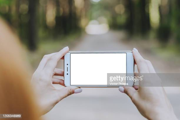 mockup smartphone in the hands girls in the forest, against a background of trees. - iphone mockup stock pictures, royalty-free photos & images