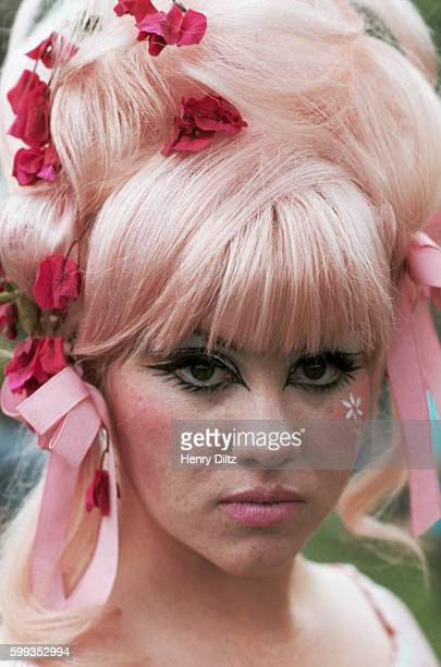 A mod girl wears a pink tint in her beehive hairdo with pink ribbons and pink flowers to a in