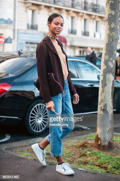 Model Aaliyah Hydes wears a brown jacket blue jeans white sneakers and an embellished choker necklace after the Valentino show on March 04 2018 in...