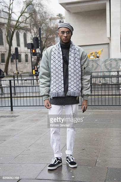 Model Aaron Jamael Marx wears a vintage jacket Levi's jeans Vans trainers Week day sweater and hat and a Funtime clothing scarf day 2 of London Mens...