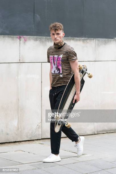 Model Aaron Lesta wears Blood Brothers trainers and T shirt Axel Arigato trousers KTZ socks and a vintage scarf on day 3 of London Collections Men on...