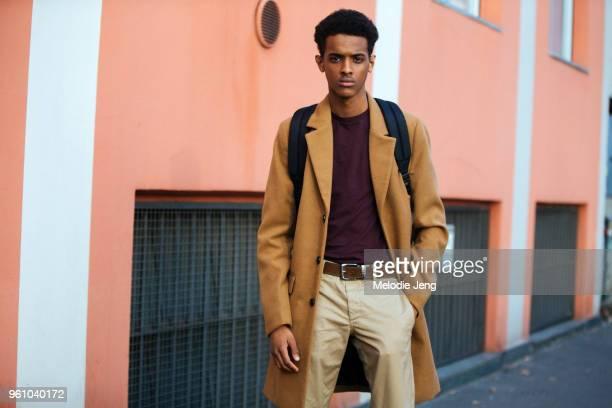 Model Abdou Alios wears a camel coat, purple top, and khaki pants during Milan Men's Fashion Week Fall/Winter 2018/19 on January 14, 2018 in Milan,...