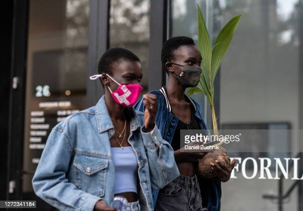 Model Achenrin Madit is seen holding a plant outside the Jason Wu show during New York Fashion Week S/S21 on September 13, 2020 in New York City.
