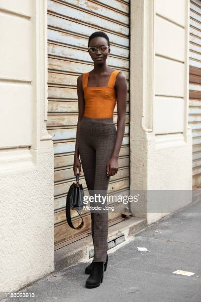 Model Achenrin Madit wears clear cateye sunglasses an orange tanktop brown check pants black bag and black boots after the Boss show during Milan...