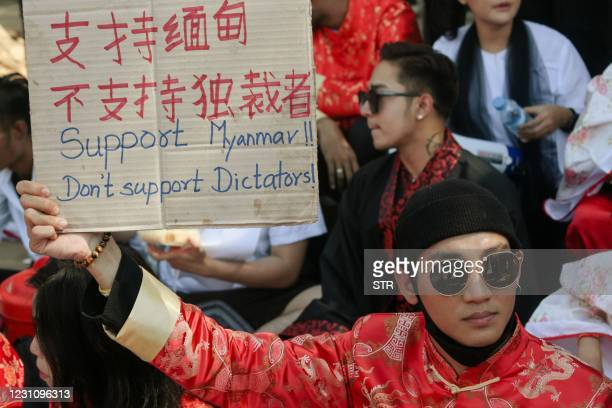 Model, actor and singer Paing Takhon wears a traditional Chinese outfit while holding a sign during a demonstration against the military coup in...