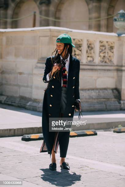 Model Adesuwa Aighewi attends the Thom Browne show in a long black Thom Browne coat red and blue tie green backwards cap and black loafers during...