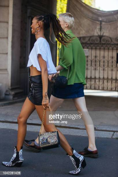 Model Adesuwa Aighewi exits the Etro show in a white cropped shirt mini black leather skirt cowboy boots embellished purse during Milan Fashion Week...