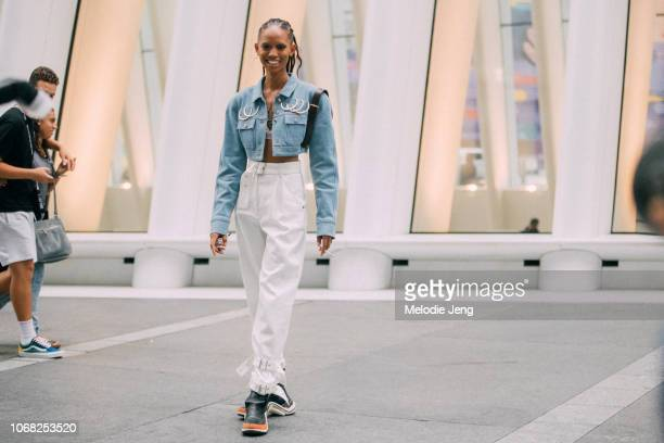 Model Adesuwa Aighewi in a cropped blue jacket with rings white pants black Louis Vuitton Archlight sneakers after the Longchamp show during New York...