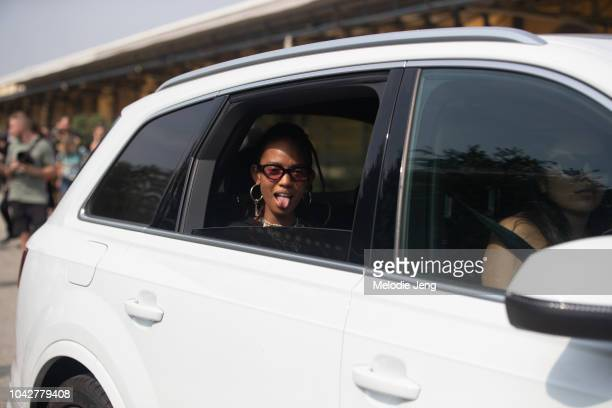 Model Adesuwa Aighewi sticks her tongue out from her car after Roberto Cavalli during Milan Fashion Week Spring/Summer 2019 on September 22 2018 in...