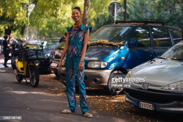 Model Adesuwa Aighewi wears a blue print jumpsuit from Nigeria fur loafers during Milan Fashion Week Spring/Summer 2019 on September 20 2018 in Milan...