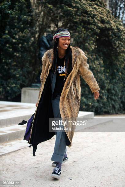 Model Adesuwa Aighewi wears a headband long fur coat gray suit jacket and pants black Fendi tshirt and black Vans sneakers after the Dior show on...