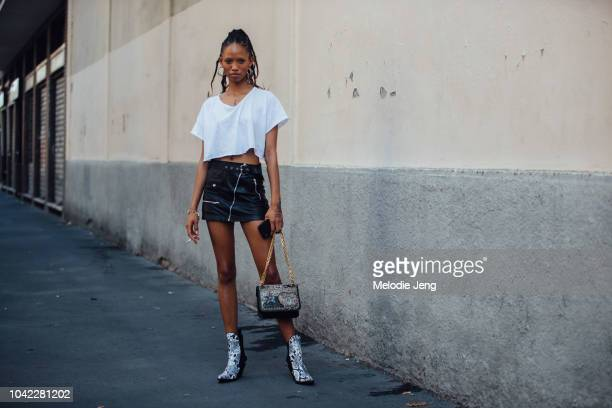 Model Adesuwa Aighewi wears a white cropped shirt mini black leather skirt cowboy boots embellished purse during Milan Fashion Week Spring/Summer...