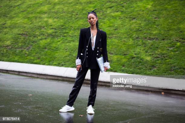 Model Adesuwa Aighewi wears earphones a black blazer black leather pants and white Yeezy sneakers during Paris Fashion Week Spring/Summer 2018 on...