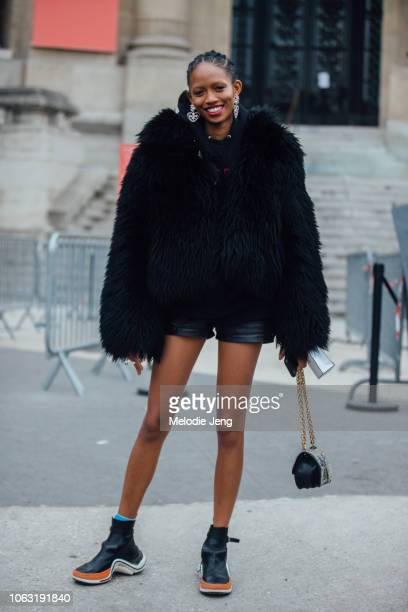Model Adesuwa Aighewi wears heart earrings a black fur jacket black leather shorts and black Louis Vuitton Archlight boots after the Chanel show...