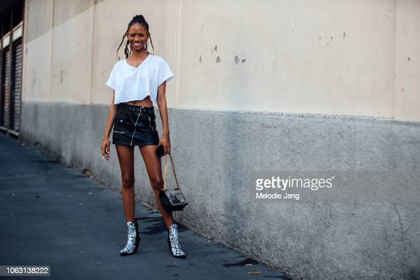 Model Adesuwa Aighewi wears hoop earrings a cutoff white shirt black leather miniskirt white crocodile leather boots and an embellished purse after...