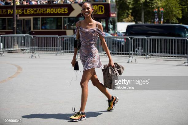 Model Adesuwa Aighewi wears large ring earrings a purple velvet dress yellow Nike sneakers after the Chanel show during Couture Fall/Winter 2018...