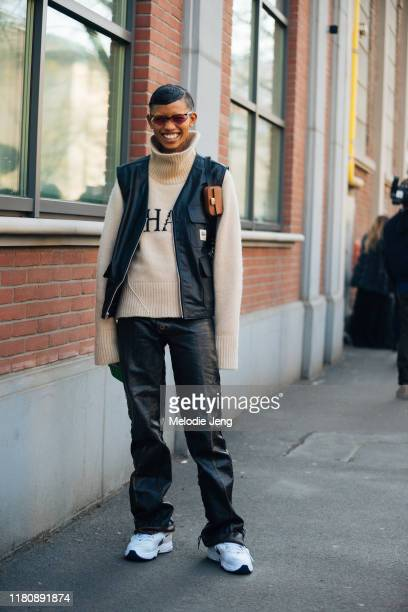 Model Adesuwa Aighewi wears red Fendi sunglasses a tan Khaite knit turtleneck Studdy leather vest mini Fendi bag black leather pants and white Nike x...