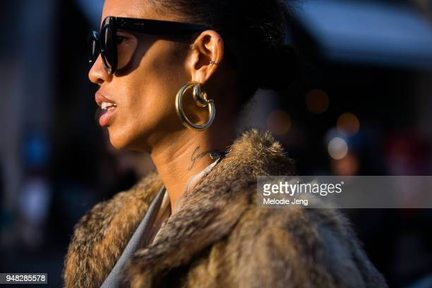 Model Adesuwa Aighewi weasr black Celine sunglasses a large gold doublering shaped earring and a tattoo on her neck during London Fashion Week...