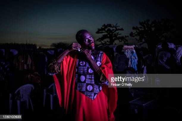 Model adjusts her earring backstage during an outdoor show at Dakar Fashion week on December 12, 2020 just outside Dakar, Senegal. With Senegal's low...
