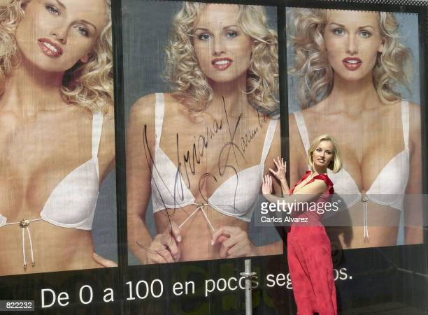 Model Adriana Karembeu stands by an autographed billboard poster as she is introduced as the model for a new publicity campaign for Wonderbra April 4...
