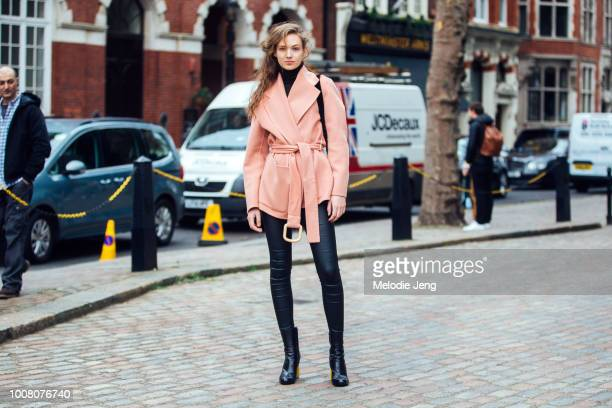 Model Adrienne Juliger wears a pink robed jacket leather leggings and black boots on Day 3 of the London Fashion Week February 2017 collections on...