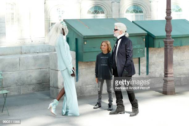 Model Adut Akech Hudson Kroenig and Chanel Stylist Karl Lagerfeld acknowledge the applause of the audience at the end of the Chanel Haute Couture...
