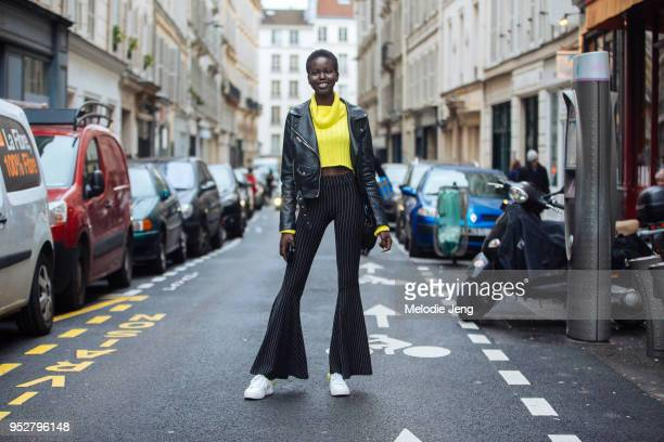 Model Adut Akech wears a black leather jacket yellow sweater black pinstripe flare jeans and white sneakers on January 23 2018 in Paris France