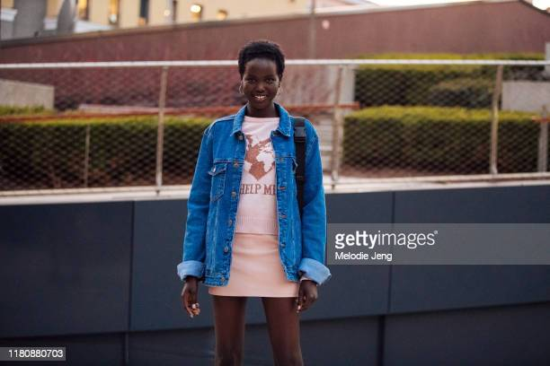 """Model Adut Akech wears a denim jacket and pink Alberta Ferretti """"Help Me"""" earth environmentalist sweater and a short pink skirt after the Alberta..."""