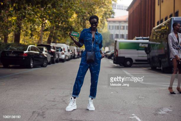 Model Adut Akech wears a denim pretty sure jumpsuit black Jil Sander bag and white boots during Milan Fashion Week Spring/Summer 2019 on September 20...