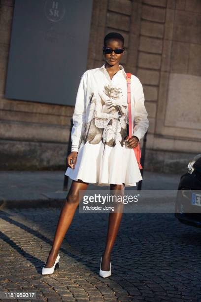 Model Adut Akech wears a graphic fine art white dress and white heels after the Valentino show during Couture Fashion Week Fall/Winter 2019 on July...
