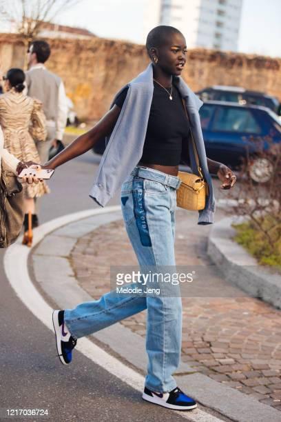 Model Adut Akech wears a purple sweater on her shoulders, yellow Fendi bag, blue Prada 019 Jeans, and Nike Jordan sneakers after Prada during Milan...
