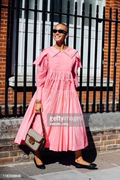 Model Adwoa Aboah attends the Molly Goddard dress in black sunglasses, a pink dress, brown Gucci bag, and black ballet flats during London Fashion...